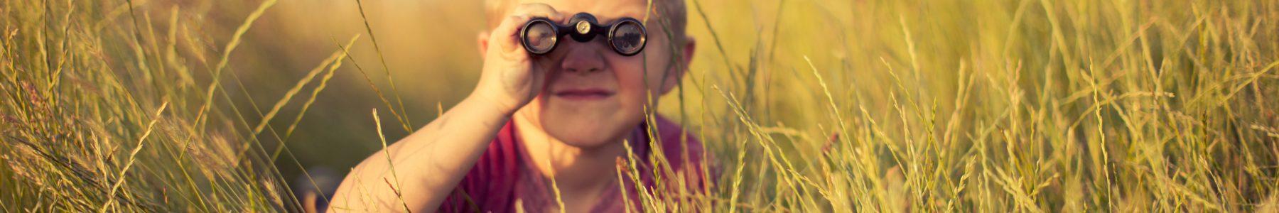 Kind versteckt sich und blickt durch ein Fernrohr - ©RichVintage - iStock.com