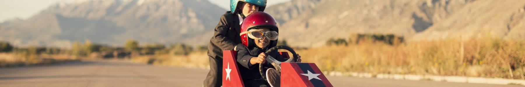 Zwei Kinder in einem Rennwagen - ©RichVintage - iStock.com